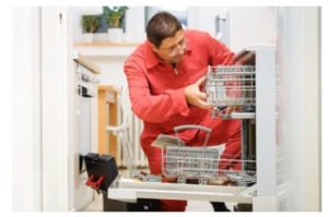 repairman fixing a broken dishwasher in the kitchen