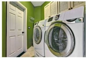 Small bright green laundry room inter with washer and dryer.