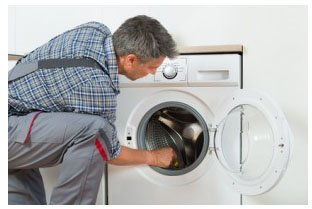 technician Checking Washing Machine At Home