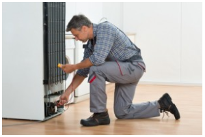 Technician Checking Fridge With Multimeter At Home in Sydney, NSW.